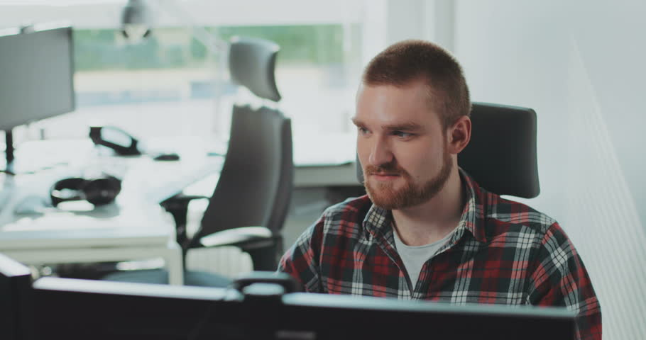 A young bearded man sits at a computer. Works in the office. Feels happy. Face, monitor, online, professional, table, workplace, architect. Contemporary design. Shot on RED Epic Camera.   Shutterstock HD Video #31727758