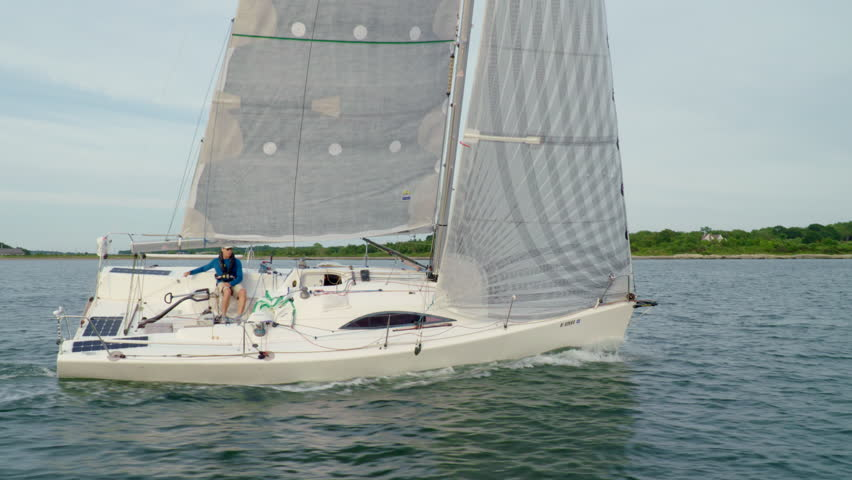 Experienced solo sailor sailing on the ocean as the bar races along.  Shot from chase boat.