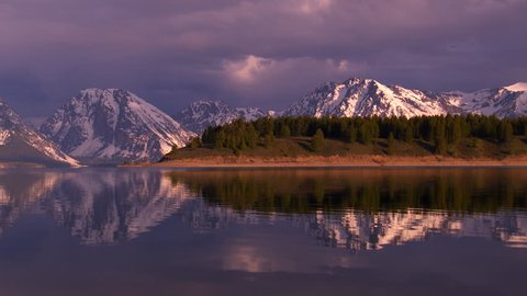Grand Teton National Park - snow-capped mountain peaks at sunrise with dramatic lighting and cloud formations. Reflections in water.