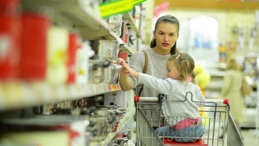 Beautiful Mother and Daughter Inside the Hypermarket Choosing Some Red Pan and Puting it in Shopping Cart. | Shutterstock HD Video #31775377