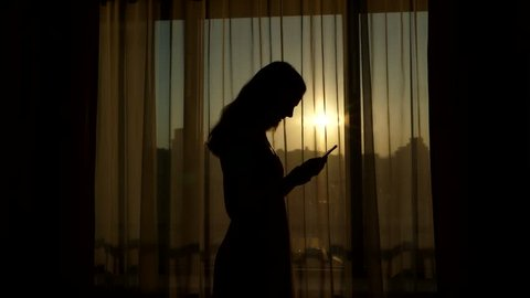 Black silhouette of young long haired woman holding in hand and looking to smartphone, stand against living room window. Bright sun seen through transparent curtain, girl stare to mobile device
