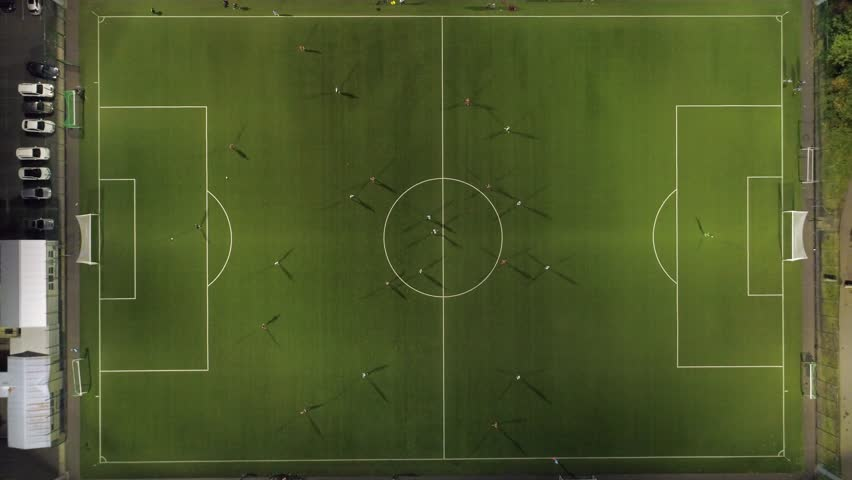 Aerial view of a soccer game being played at nighttime with floodlights lighting the field.