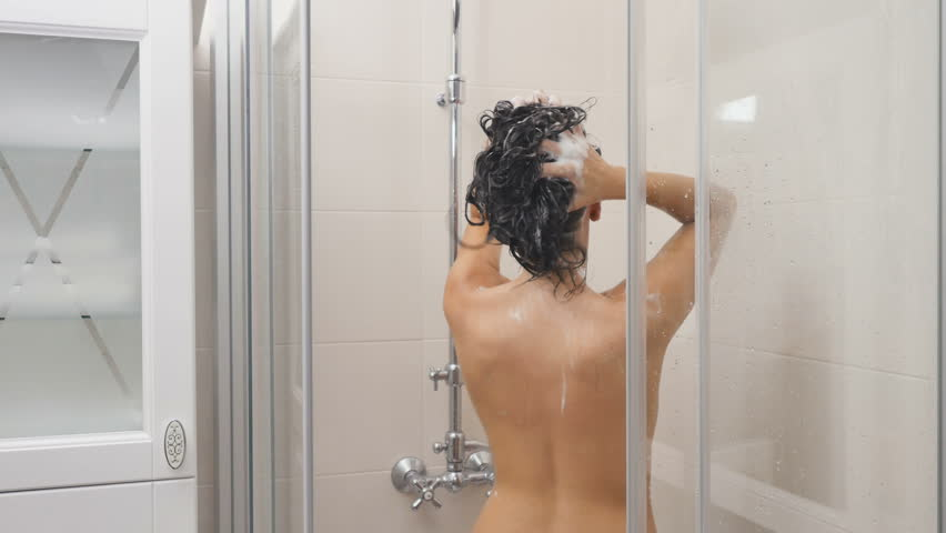 Woman washes hair in shower cabin