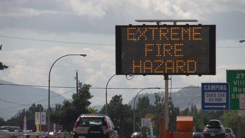 LED Road Sign: Evacuees Follow Signs - Extreme Fire Hazard - Please Use Caution. Along highway during extreme fire season in British Columbia. Vernon, BC. Long Shot