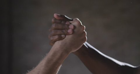Two men, one European and one African American, give their hand as a sign of friendship and respect in sport. Concept of: bond, sport, fight against racism.