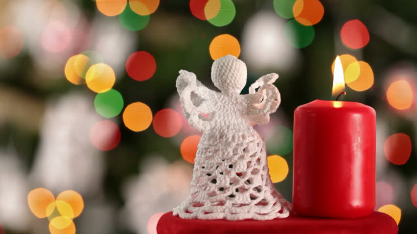 crocheted xmas angel and burning candle against blurry christmas tree with blinking lights hd stock - Candle Christmas Lights