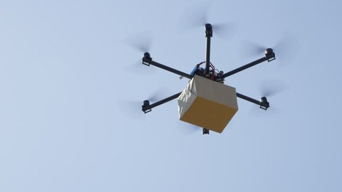 CLOSE UP UAV drone delivery. Multicopter flying big brown package over blue sky. Drone delivering post package to your home. Futuristic shipment by helicopter drone. Multirotor logistics and transport