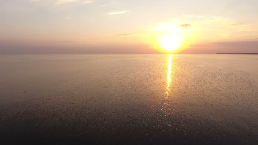 An inspiring bird`s eye shot of shining sea waters at a picturesque sunset on a sunny day in summer. The drifting waves are covered with a marvelous sun path. The skyscape is multicolored.  | Shutterstock HD Video #31856476