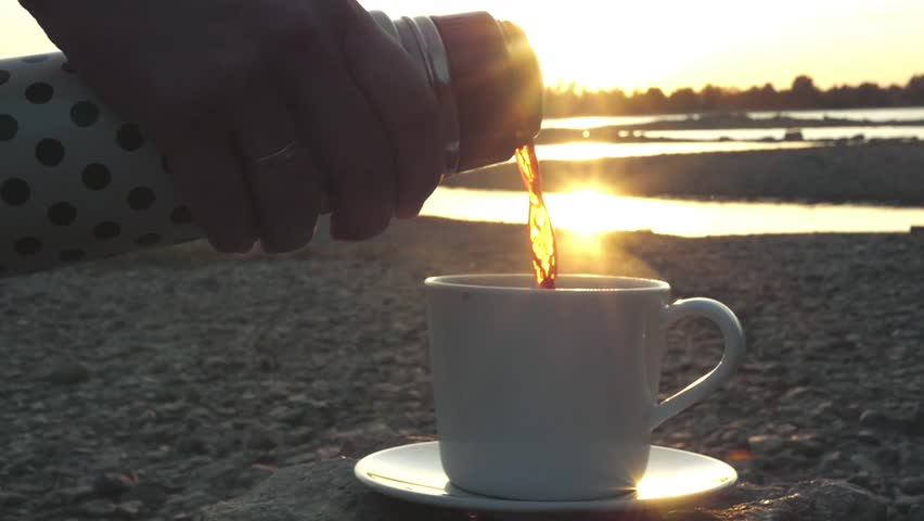 Pour a cup of invigorating fragrant drink from a thermos at sunset with beautiful rays from the sun. close-up, slowmotion, 1920x1080, hd