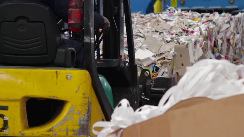 Loader sorts the pallets with the recycled material at the waste processing plant.   Shutterstock HD Video #31869436