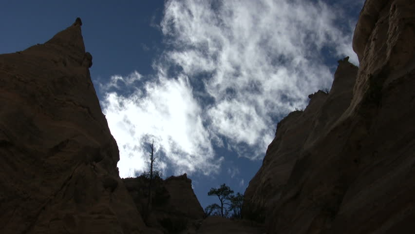 HD time lapse of white clouds moving behind the tall rock and dirt formations at Kasha Katuwe Tent Rocks National Monument