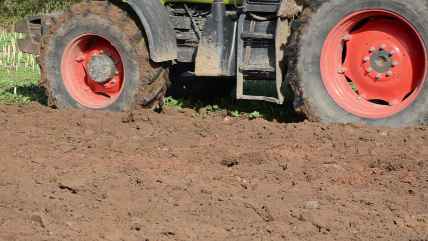 closeup of heavy agricultural machine plough field soil.