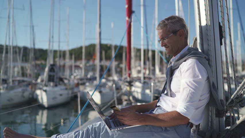 Successful Senior Man Businessman using Laptop for Shopping Online with Credit Card on Yacht at Sunset | Shutterstock HD Video #31876516