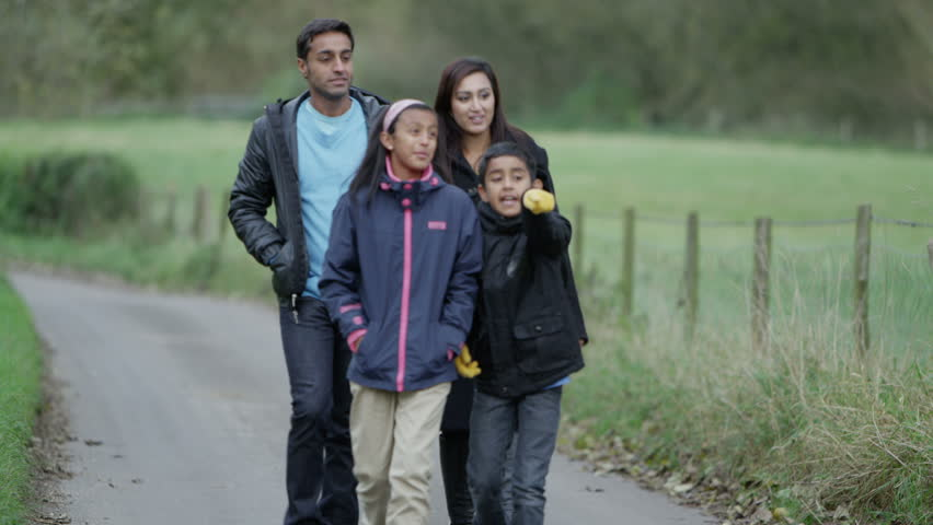 Happy family of 4 enjoying some fresh air and a walk. Slow motion.