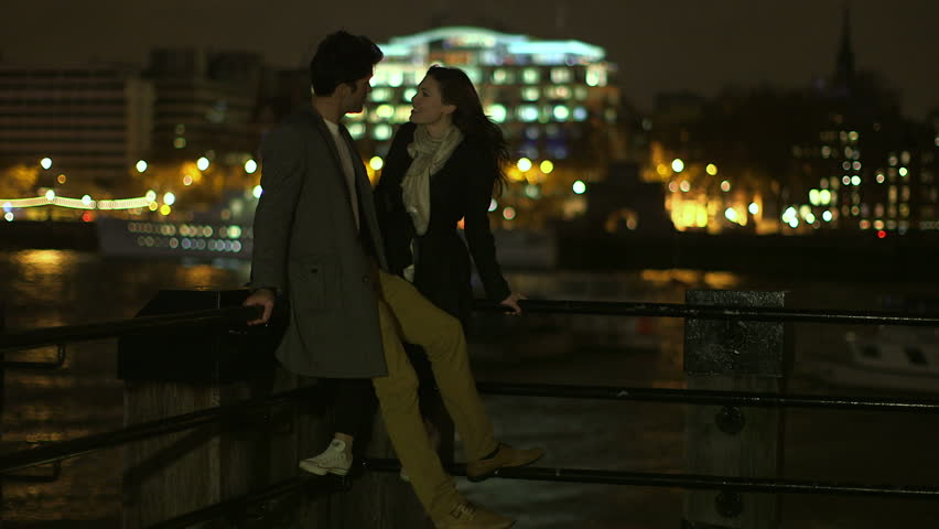 An attractive man and a woman are spending time together in London at night. They are overlooking the river Thames and the illuminated skyline. An illuminated barge passes through the shot.