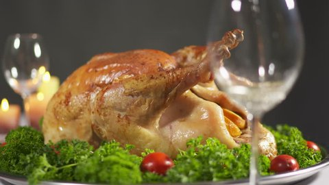 Thanksgiving turkey dinner. Roasted Thanksgiving or Christmas turkey steaming on tray. Burning candles in the background. Pouring white wine into wine glass.