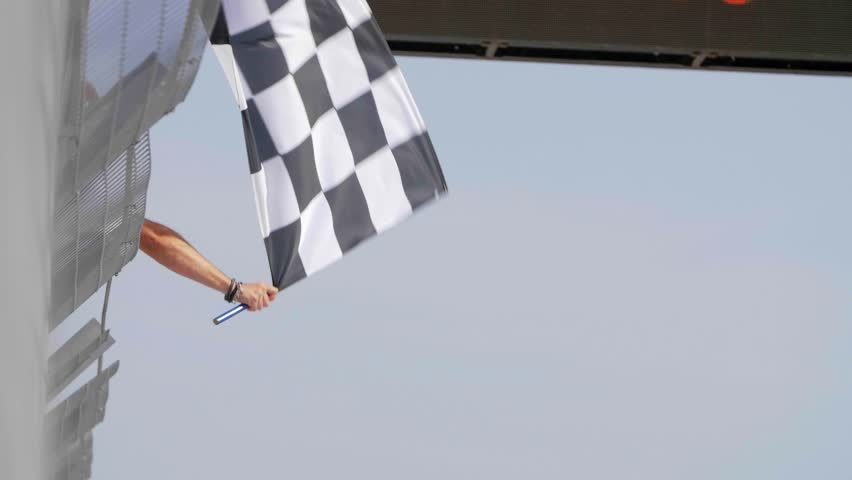 Man holding and waving Checkered race flag in slow motion at finish line on a raceway.  | Shutterstock HD Video #31921816