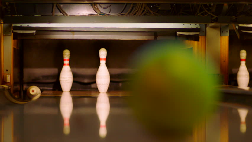 Bowling ball knocking pins on the bowling lane. Slow motion