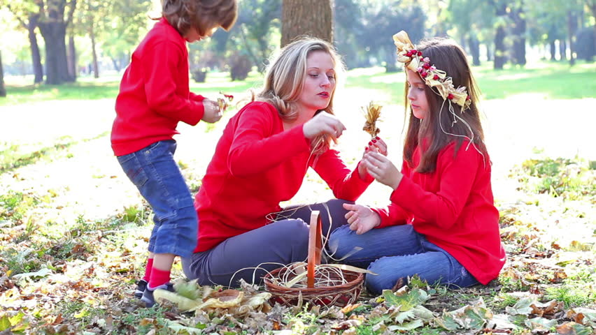 Mom and daughter in the park make a garland of flowers, Focus on the mum and children