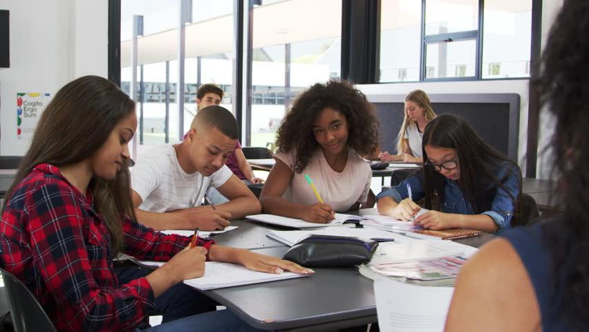 High school kids raise hands, teacher sitting at their desk | Shutterstock HD Video #31947376