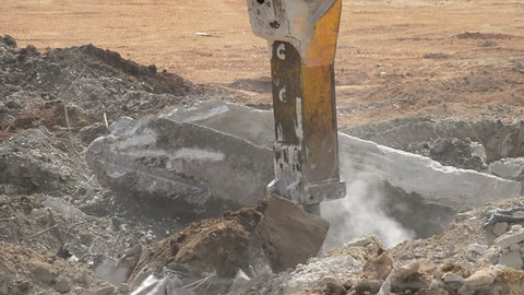Excavator hammer working with debris in the demolition of a building