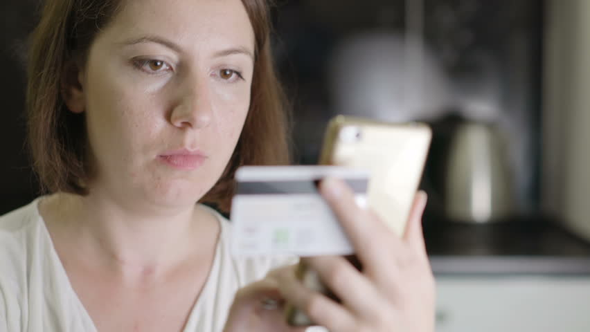 Girl enters credit card number on a smartphone | Shutterstock HD Video #31976974