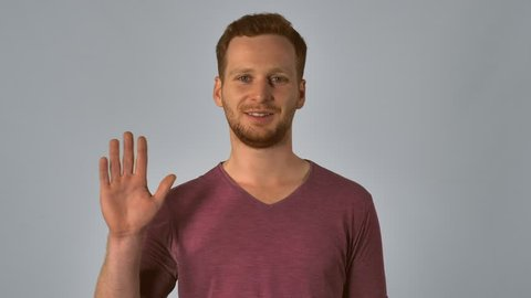 friendly caucasian guy with red hair posing showing hand gesture hello. handsome redheaded men wearing in casual t-shirt. Portrait ginger young caucasian man on grey background
