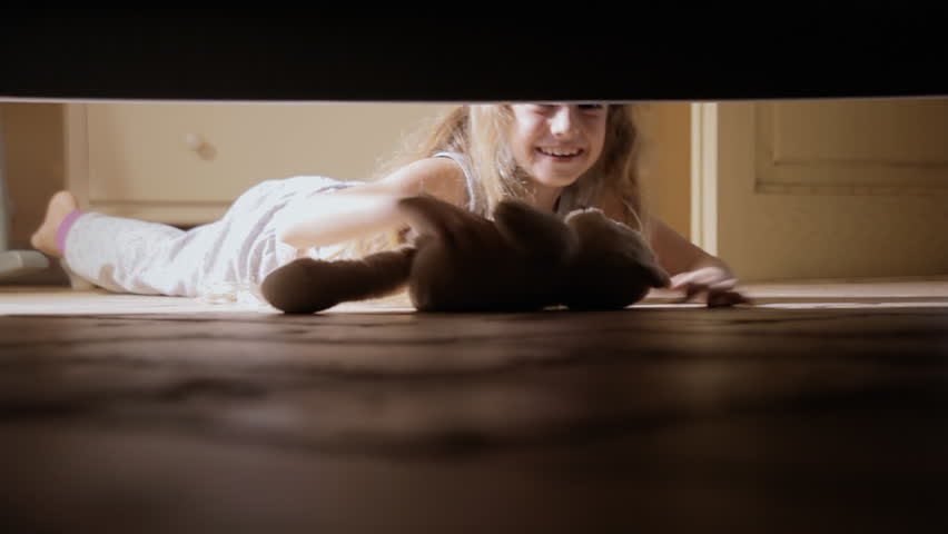 A little girl finding her beloved teddy bear under the bed. Close-up shot.