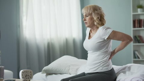 Blond mature lady sitting on bed and touching her back, radiculitis and pain