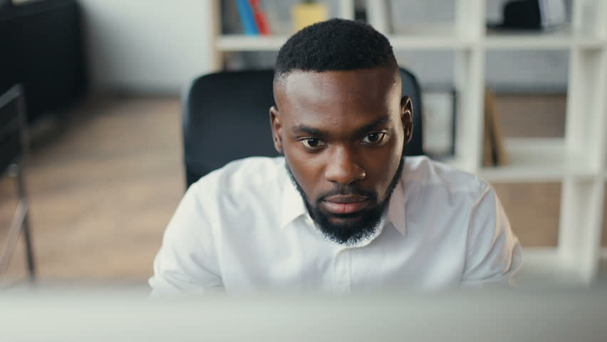 African American handsome male uses computer for work in modern office programmer serious looks at monitor screen freelance successful worker businessman solves engineering problems Slow motion