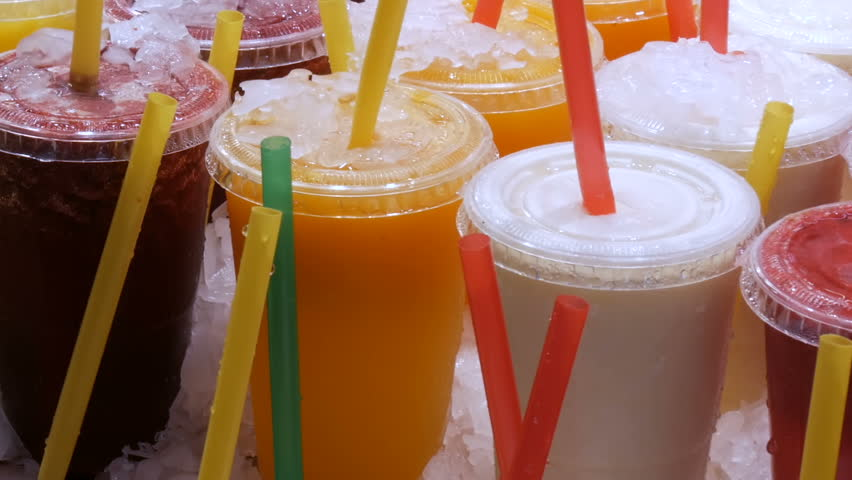 Smoothies juice or fresh in plastic cups with colored straws on the counter of the fruit market | Shutterstock HD Video #32045266