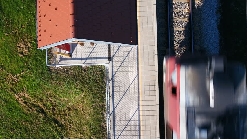 Cargo Train Passing The Railway Station Aerial Top View 4K. Static Flying  Directly Above The