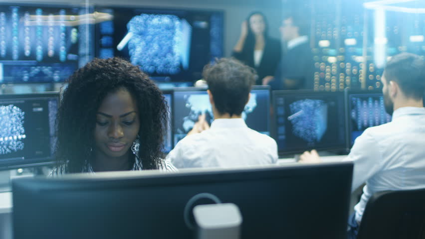 Female Computer Engineer Works on a Neural Network/ Artificial Intelligence Project with Her Multi-Ethnic Team of Specialist. Office Has Multiple Screens Showing 3D Visualisation.Shot on RED EPIC-W 8K