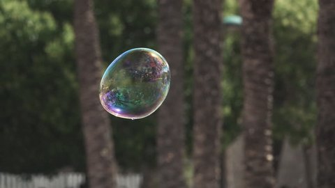 Super slow motion of big soap bubble exploding in the air