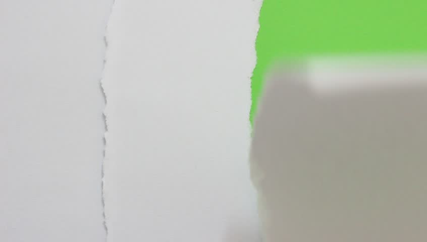 Close up of paper tearing into green screen background