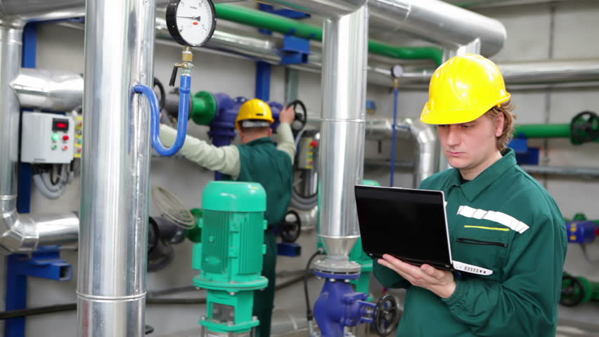 Industrial workers with notebook working in power plant, happy and satisfied teamwork