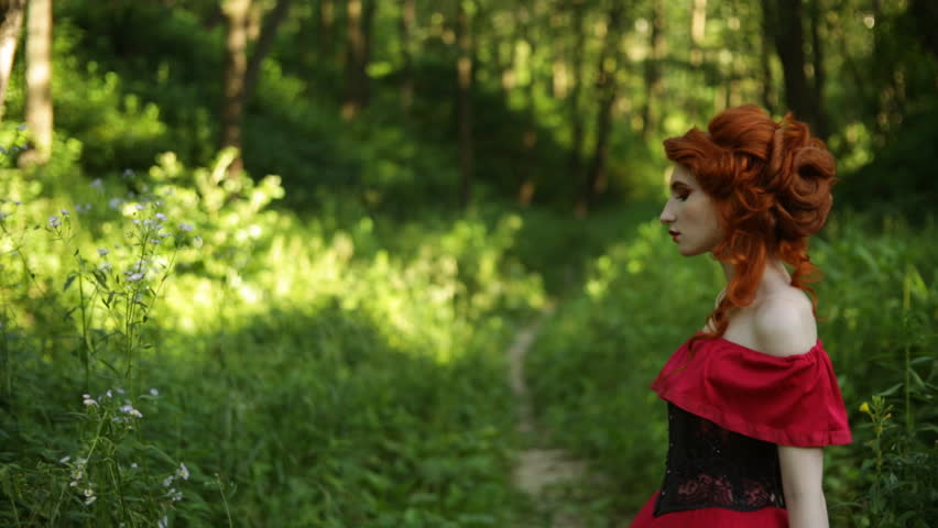 Beautiful red-haired girl in red dress posing on green background. Portrait of a woman with red hair in a summer forest