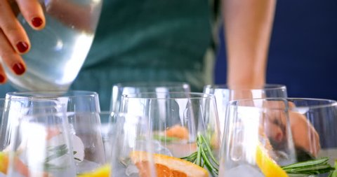 Woman pouring tonic soda water into glasses, preparing alcoholic beverages at a party