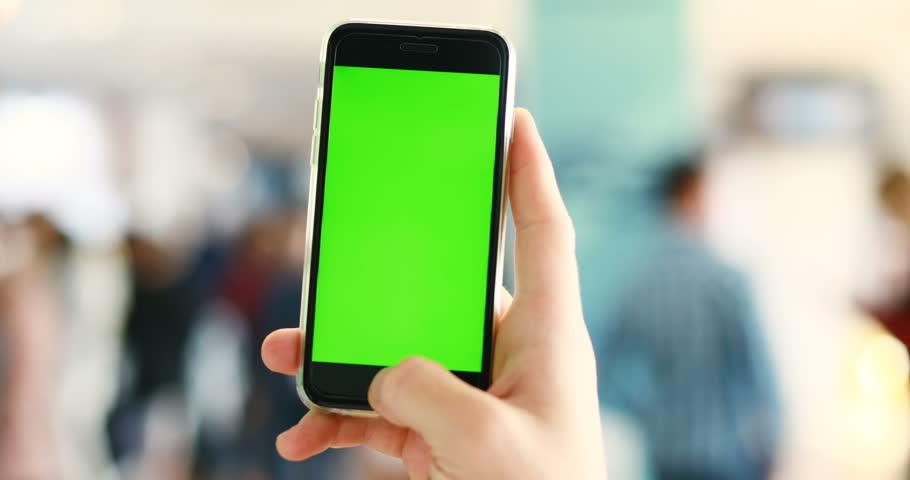 LVIV, UKRAINE - 2017: Man hand holding using green screen smart phone chromakey display public space | Shutterstock HD Video #32115826