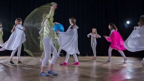 A girl with a big blue ball is dancing in the middle o a stage and the rest of the girls are dancing around her.