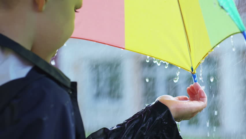 Cinemagraph of little boy holding umbrella and catching raindrops in his palm while standing under heavy rain