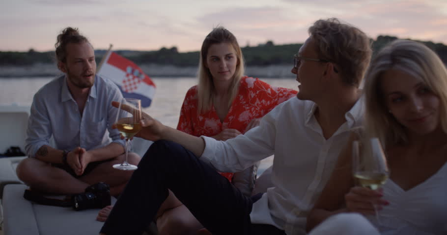 Group of Young People Talk, Drink Champagne in the Stern of the Moving Yacht. They Have Great Vacation. In the Background Island with Small Village. Shot on RED Epic 4K UHD Camera. #32176156