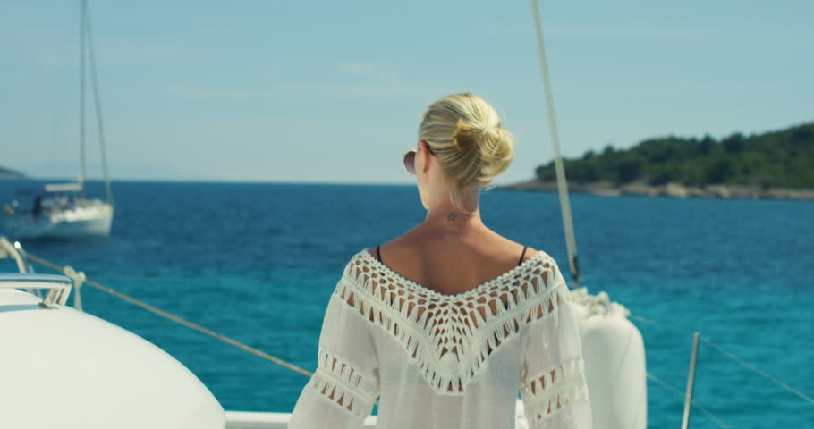 Following Shot of a Beautiful Woman Walking on the Yacht's Deck. Sun Shines, Islands and Azure Sea in the Background. Shot on RED Epic 4K UHD Camera.