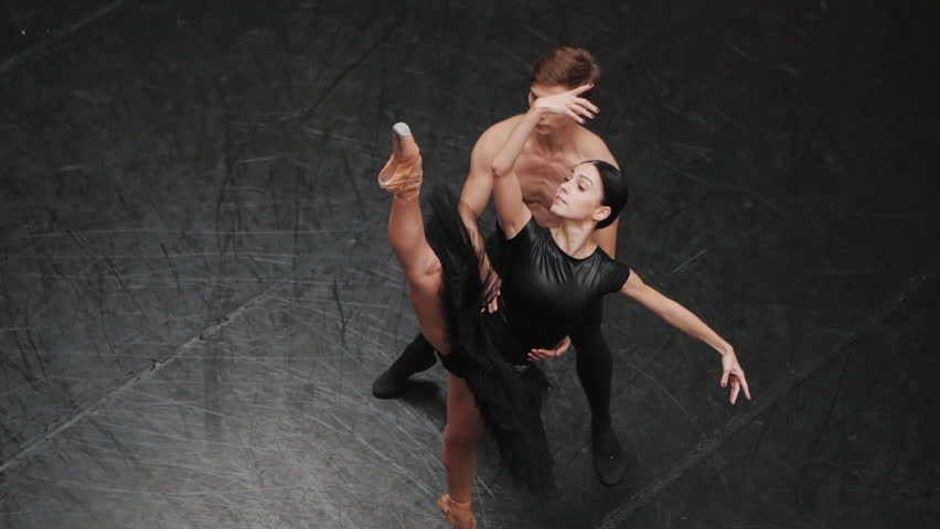 Young man practicing in classical ballet with young beautiful woman in black clothing in the gym. Minimalism interior, sensual dance. Training before the performance. Slow motion. Top view