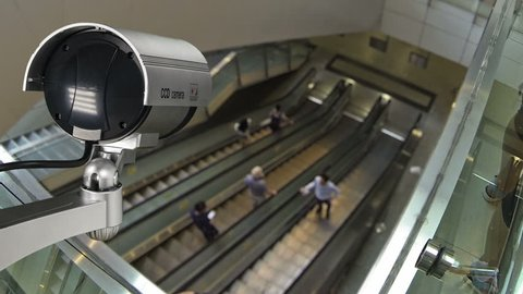 Closeup CCTV security camera operating with escalator system and people