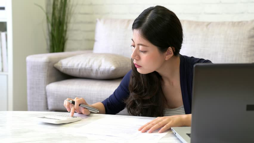 mixed race asian chinese housewife calculating accounting new year budget checking bill paper using calculator and laptop sitting on sofa in the living room at home