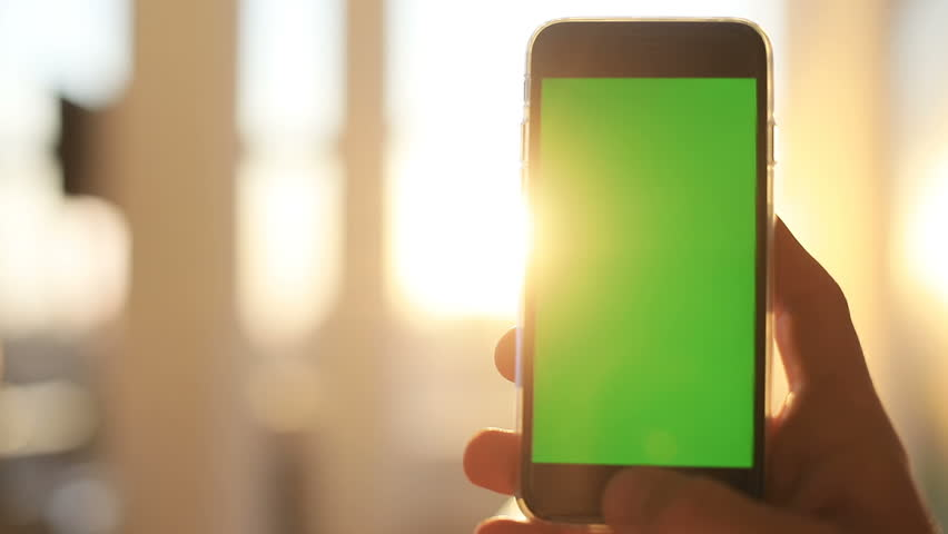 close up man hand holding black telephone smart phone green screen chroma key golden sun light sunshine background sunny day internet searching application store notification weblink online video call