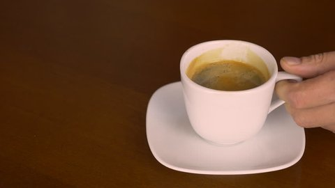 Close up white cup of freshblack coffee espresso. Hand take coffee drink and put back on plate. Wooden table derk brown color. Coffee drinking concept for coffee lovers caf restorante barista.