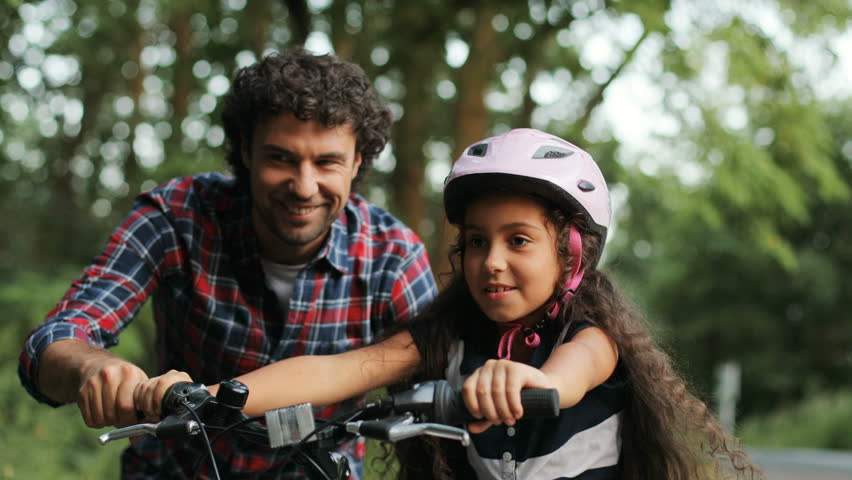 Closeup. Portrait of a little girl. Her dad is teaching her to ride a bike. He lets her go. Happy girl. Moving camera. Blurred background | Shutterstock HD Video #32235646