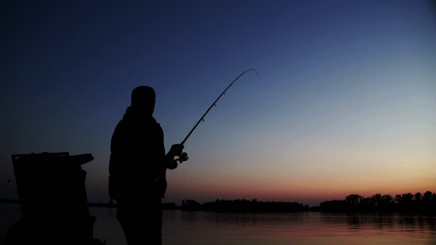 Silhouette successful fisherman catching fish and spinning fishing reel on background evening sunset. Beautiful evening sunset during fishing on river | Shutterstock HD Video #32257246